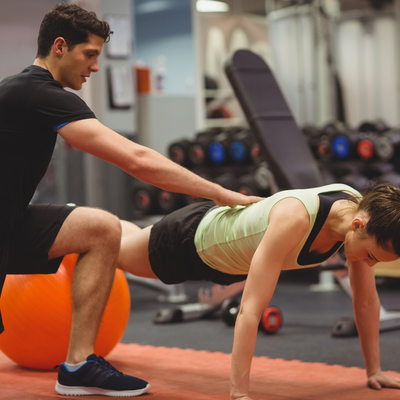 Personal trainer helping out client